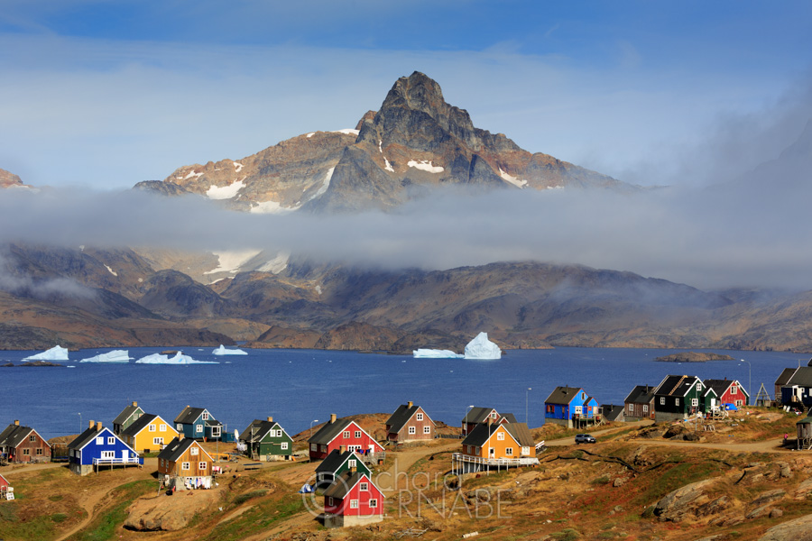The colorful houses of Tasiilaq and  Polhejmfjell Mountain, East Greenland. Tasiilaq